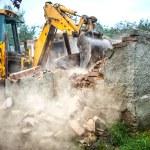 Bulldozer demolishing concrete brick walls of small building — Stock Photo #56066727