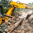Industrial excavator and bulldozer loading debris and demolition concrete walls into a container — Stock Photo #56066711