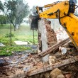 Excavator demolishing a concrete wall.bulldozer loading demolition debris and concrete waste for recycling at construction site. — Stock Photo #56066729