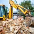 Industrial hydraulic excavator on construction and demolition site, recycling construction waste with bulldozer — Stock Photo #56066747