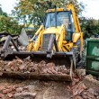 Industrial excavator and bulldozer loading debris and demolition bricks into a container — Stock Photo #56066749