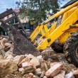Bulldozer loading demolition debris and concrete waste for recycling at construction site — Stock Photo #56066753