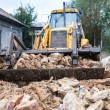 Bulldozer demolishing an old building and carrying debris — Stock Photo #56066761