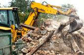Industrial excavator and bulldozer loading debris and demolition concrete walls into a container — Stock Photo