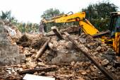 Hydraulic crusher, industrial excavator machinery working on a rainy site demolition — Stock Photo
