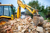 Industrial hydraulic excavator on construction and demolition site, recycling construction waste with bulldozer — Stock Photo