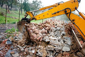 Excavator on demolition site loading bricks and concrete walls — Stockfoto