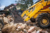 Bulldozer loading demolition debris and concrete waste for recycling at construction site — Stock Photo