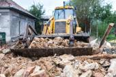 Bulldozer demolishing an old building and carrying debris — Stock Photo