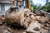 Industrial hydraulic backhoe bulldozer loading demolition debris, stone and concrete for recycling — Stockfoto
