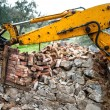 Bulldozer on demolition site working on an old building and loading bricks and concrete — Stock Photo #56163039