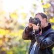 Photographer with professional digital camera taking pictures in nature — Stock Photo #58136419
