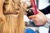 Blonde woman at hair salon using a professional tool for creating curls with long lasting effect. Beautiful woman using diferent styling salon tools — Stock Photo