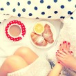 Close-up of woman legs and breakfast in bed with croissants, coffee and orange juice on a lazy sunday morning — Stock Photo #60015531