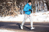 Young athlete going for a run outdoor in snow, hardcore training and jogging — Stock Photo