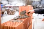 Construction site on a winter day with worker building brick walls with mortar and bricks — Stockfoto