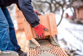 Close-up of construction worker, bricklayer building new house with brick walls — Stock Photo