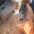 Male worker cutting bricks with angle grinder power tool, dust and debris on construction site — Stock Photo #65402447