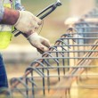 Worker hands using steel wire and pliers to secure bars on construction site and preparing for concrete pouring — Stock Photo #65402543