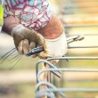 Worker hands using steel wire and plincers to secure steel bars, preparing for concrete pouring on construction site — Stock Photo #65402553