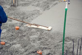 Mason building and leveling a first layer of fresh concrete floor at house foundation, construction site — Stock Photo