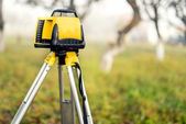 Surveying measuring equipment level theodolite on tripod on a foggy day in construction site — Stock Photo