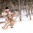 Professional hunter with sniper rifle aiming and shooting during winter — Stock Photo #65837877