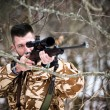 Hunting, army, military concept - sniper holding rifle and aiming at target in the forest during operation — Stock Photo #65837891