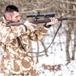 Hunter with sniper aiming and shooting in the forest during winter hunting season — Stock Photo #65838177