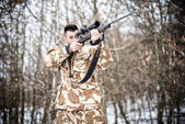 Sniper with weapon ready for combat or hunting in the forest on a winter day — ストック写真