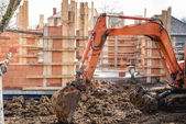 Track-type excavator loader working on earth and loading at house construction site — Photo