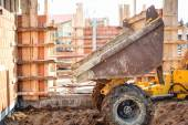 Dumper truck unloading gravel, sand and stones at construction site. Bricklayering and working at construction site  — Stock Photo