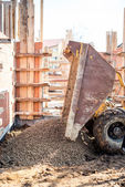Dumper truck unloading construction gravel, granite and crushed stones at building foundation — Stock Photo