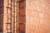 Reinforcement steel bars on pillars, walls and layers of bricks on new house construction - details of building structure on construction site — Stock Photo