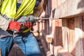 使用功率钻在建筑工地上的工人,在砖中创建孔 — 图库照片