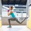 Female runner stretching and doing squats after jogging training. Fitness concept on stadium — Stock Photo #71807807