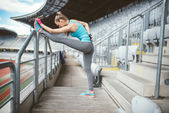 Fitness young woman stretching outdoors and doing warm up exercises. Training and working out sportswoman concept. Vintage, soft effect on photo — Stock Photo