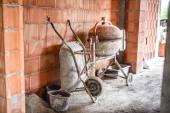 Cement mixer machine, wheel barrow and other construction site tools after working hours — Stock Photo