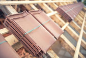 Brown roof tile packs at house construction site. Roof under construction with modern tiles — Stock Photo