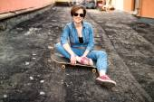 Portrait of brunette girl, hipster woman with skateboard, sunglasses and jeans outfit. — 图库照片