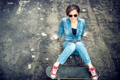 Modern girl with skateboard and sunglasses posing and smiling while sitting on terrace. Hipster girl wearing sunglasses and playing with skateboard — Stock Photo
