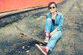 Brunette girl with skateboard sitting, smiling at camera, wearing jeans and modern outfit. Instagram filter, modern concept of healthy life — Stock Photo