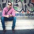 Portrait of handsome man with phone in hand, casually dressed with shirt, jeans and sunglasses against graffiti painted wall. Stylish european man travelling and taking pictures with mobile phone — Stock Photo #77727054
