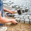 Construction worker installing stone blocks on pavement, street or sidewalk construction works — Stock Photo #80052412