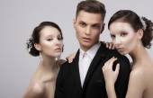 Love Triangle. Two Charming Women Hugging a Handsome Man — Stock Photo