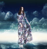 Fantasy. Luxurious Woman in Variegated Dress over Blue Sky — Stock Photo