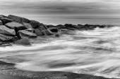 Milky waves splashing over rocks in black and white — Stock Photo