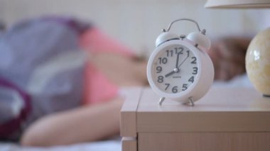 Alarm clock calls 8 am, a woman wakes up and gets out of bed — Stock Video