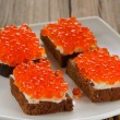 Red caviar on rye bread and butter on white plate — Stock Photo #61459487