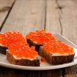 Red caviar on rye bread and butter on white plate — Stock Photo #61459491
